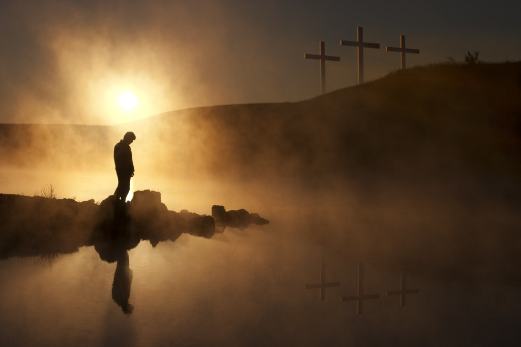 Dramatic religious photo illustration of Good Friday and Easter Sunday Morning reflecting a prayerful moment of silence with a silhouetted person bowing his head, a warm sunrise rises over a foggy lake, and three crosses on a hill reflected in the water as well.